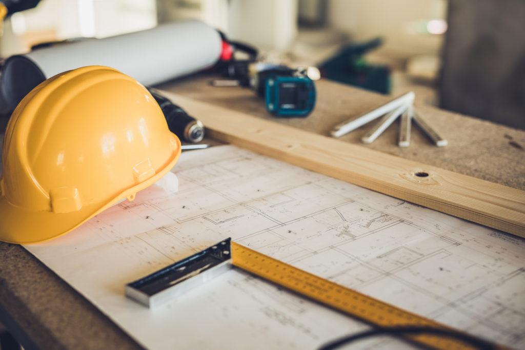 Bild på ett bord med byggritning, bygghjälm, vinkelhake och ritning