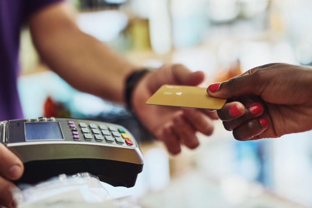 Händer som håller i ett betalkort