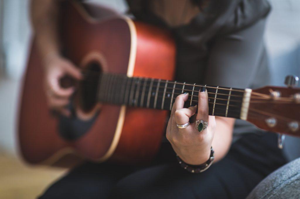 Bild på peson som spelar gitarr