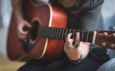 människa som spelar guitarr
