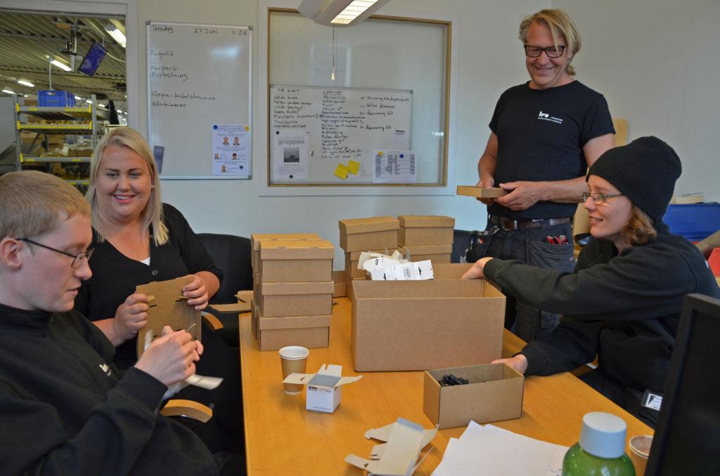 Bild på personer som arbetar i IRO-gruppen sitter vid ett gult bord där det står lådor.
