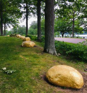 Bild på Grove Store, stora stenar målade i guld som ligger på rad längs Marbäcksvägen.
