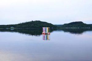 Bild på Colour in waves, en konstinstallation med en flotte med en färggrant segel ute i Åsunden
