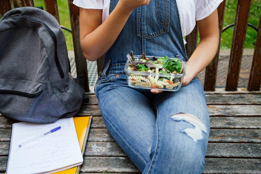 Bild på flicka i jeans som sitter på en bänk med en matlåda med pasta och sallad.