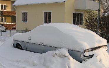 Bild på bil parkerad framför hus, gömd i snö.