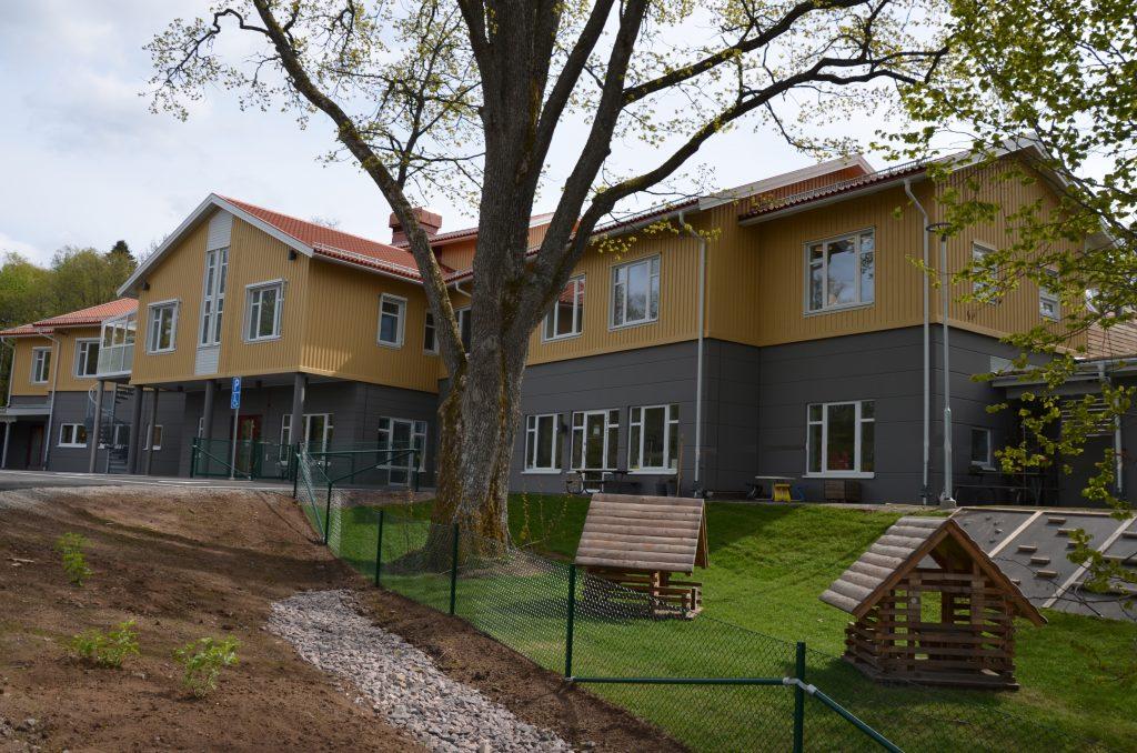 Bild på Tre Rosors förskola. En gul byggnad med hög mörkgrå husgrund. Huset har två våningar.