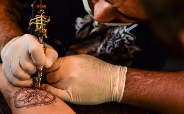 Bild på en person som gör en tatuering på en annan persons arm