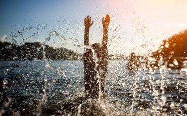 Bild på ett barn skvätter vatten i en sjö