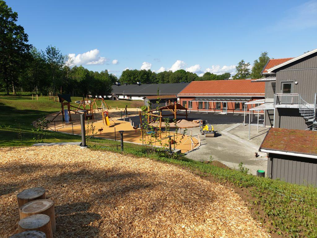 Bild på en utegård vid en förskola med olika lekredskap.