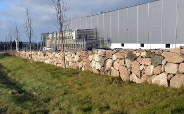 Bild på stenmur längs en väg och bakom den en industribyggnad utan fönster.