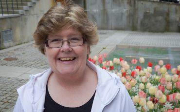 Bild på glad medelålders kvinna i glasögon med vit luvjacka med tulpaner i bakgrunden.