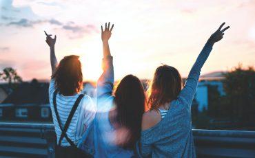 Tre ungdomar med armarna uppsträckta i luften
