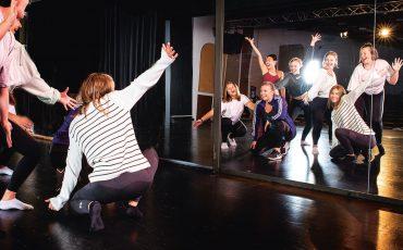 Bild på elever som övar dans framför en stor spegel