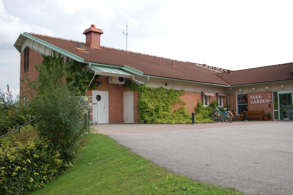 Bild på Parkgårdens entré, en låg tegelbyggnad med vita dörrar.