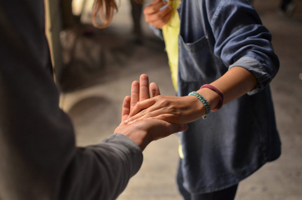 Bild på två händer som håller varandras händer