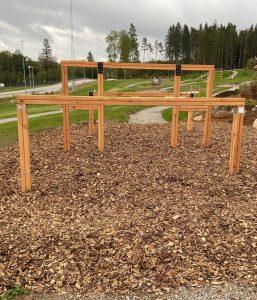 Ett trähinder på hinderbana där man ska klättra över träribbor.