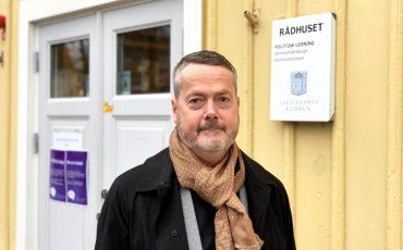 En bild på kommunchefen Gustaf Olsson, en man i 50-årsålderna som står framför en gul träbyggnad.