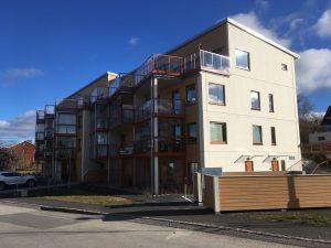 Bild på nybyggt flerbostadshus i beige med terassbalkong högst upp