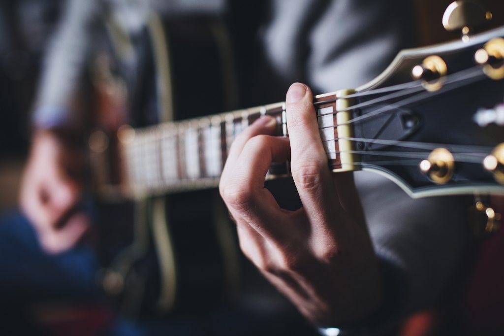En bild på en gitarrhals och en hand som tar ett ackord