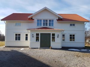 Bild på vitt villa i två våningar med rött tegel