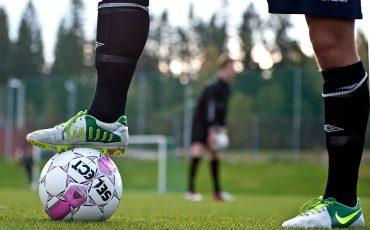 En bild på en fotbollsspelares ben som håller fast en fotboll med foten.