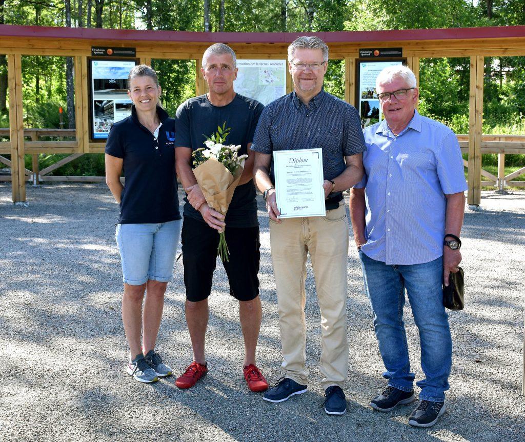 Bild på fyra personer på rad som mottagit diplom och blommor.