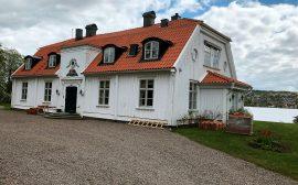 Bild på huvudbyggnaden på Brunnsnäs herrgård. En vit byggnad med tegeltak och sjön i bakgrunden.